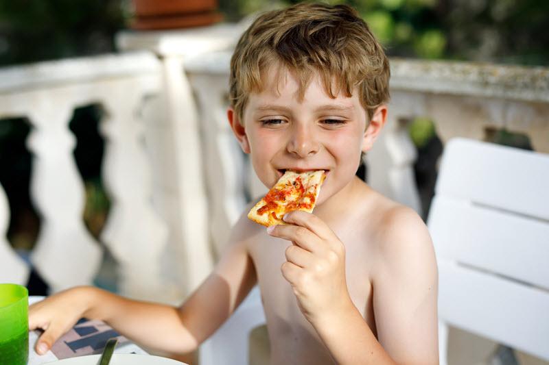 Un enfant mange une pizza